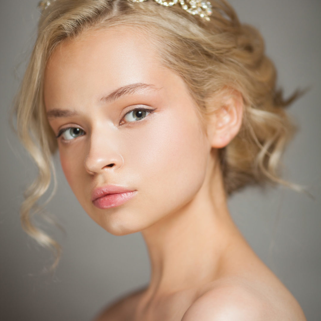 Beautiful blond woman in the image of a bride with a tiara in her hair. Picture taken in the studio on a gray background. Beauty baby face. Wedding image.