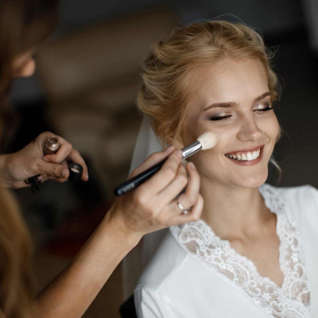 A bride is laughing while a makeup artist is putting a makeup on her face.
